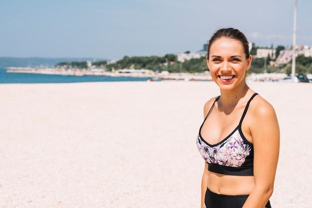 Portret van een glimlachende fitness jonge vrouw die zich op strand bevindt