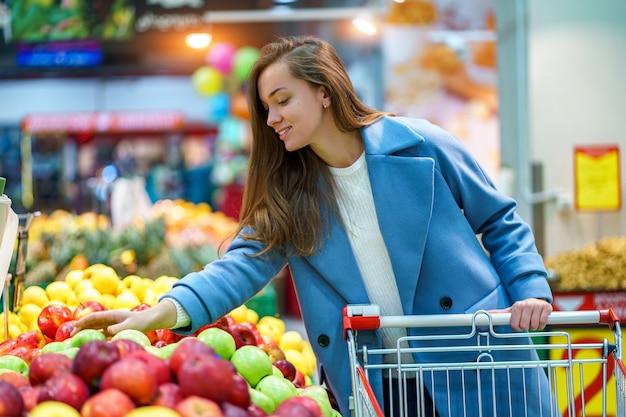 Portret van een glimlachende gelukkig aantrekkelijke jonge vrouw koper met kar in de supermarkt supermarkt tijdens het kiezen en kopen van verse appels op fruit afdeling