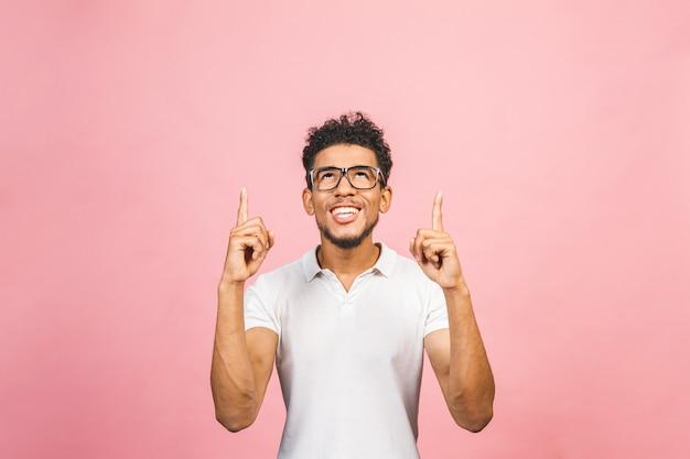 Portret van een glimlachende gelukkig afrikaanse man in casual wijzen met vingers omhoog geïsoleerd over roze achtergrond.