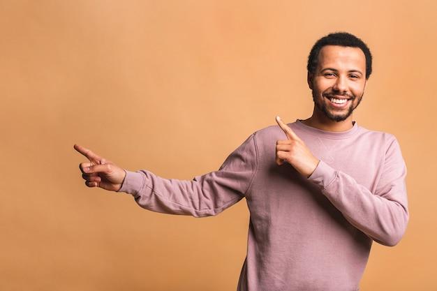 Portret van een glimlachende gelukkig man in casual wijzend met vingers opzij geïsoleerd over beige.