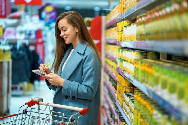 Portret van een glimlachende gelukkige aantrekkelijke jonge vrouwelijke koper met kar in de opslagdoorgang met kruidenierswinkellijst tijdens het winkelen voedsel