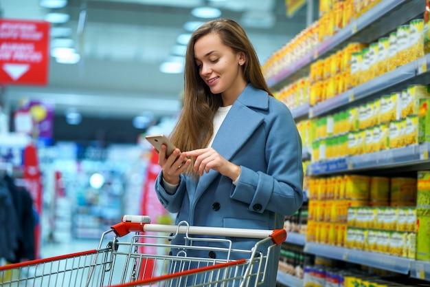 Portret van een glimlachende gelukkige aantrekkelijke jonge vrouwelijke koper met kar in de winkeldoorgang met kruidenierswinkellijst op smartphone tijdens het winkelen voedsel