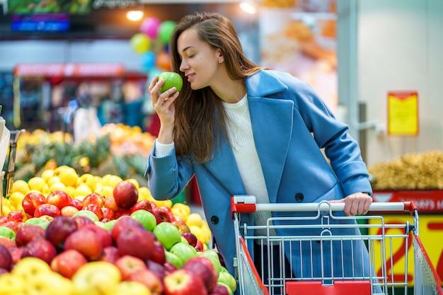Portret van een glimlachende gelukkige aantrekkelijke jonge vrouwenkoper met kar in de kruidenierswinkel tijdens het kiezen en het kopen van verse appelen bij fruitafdeling