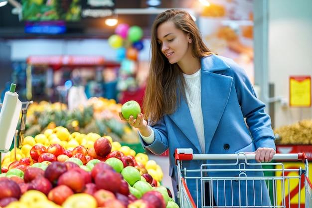 Portret van een glimlachende gelukkige aantrekkelijke jonge vrouwenkoper met kar in de kruidenierswinkelopslag tijdens het kiezen van verse appelen terwijl het kopen van vruchten
