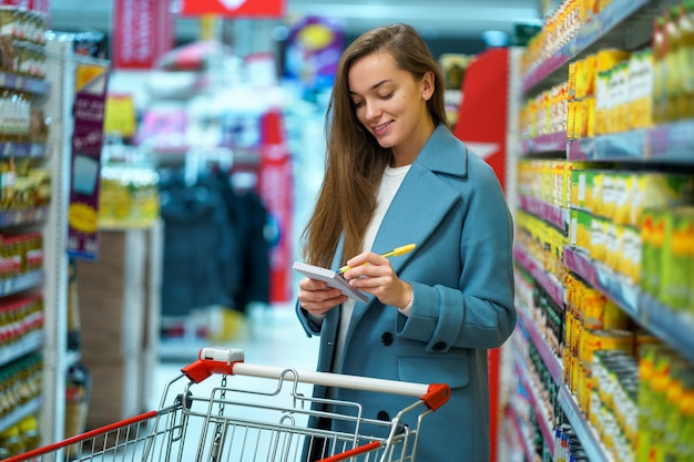 Portret van een glimlachende gelukkige aantrekkelijke jonge vrouwenkoper met kar in de opslagdoorgang met kruidenierswinkellijst tijdens het winkelen voedsel