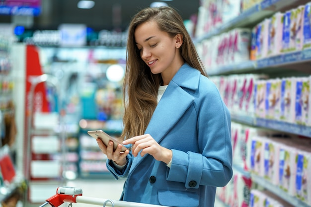 Portret van een glimlachende gelukkige aantrekkelijke jonge vrouwenkoper met kar in de supermarktdoorgang met kruidenierswinkellijst op smartphone tijdens het winkelen voedsel