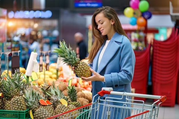 Portret van een glimlachende gelukkige aantrekkelijke vrouwenkoper met kar in de kruidenierswinkelopslag tijdens het kiezen van en het kopen van verse ananas bij fruitafdeling