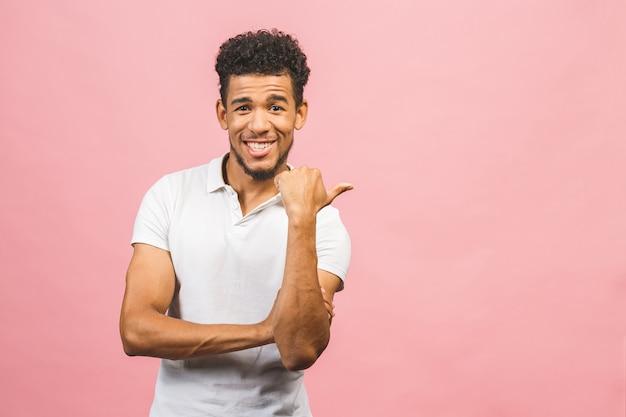 Portret van een glimlachende gelukkige afrikaanse mens in het toevallige richten met vingers opzij geïsoleerd over roze achtergrond.