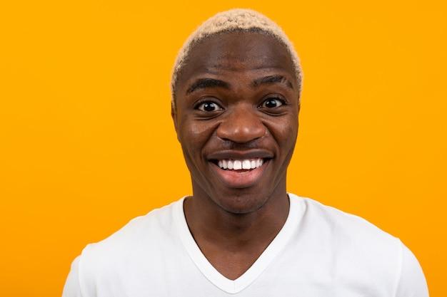 Portret van een glimlachende glimlachende charismatische afrikaanse man in een wit t-shirt op een gele studio achtergrond
