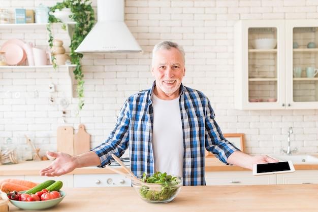 Portret van een glimlachende hogere mens die het digitale tablet in hand schouders ophalen houden