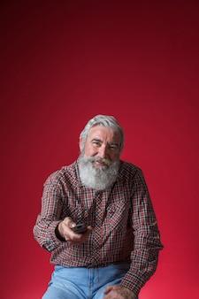Portret van een glimlachende hogere mens die het kanaal met afstandsbediening veranderen