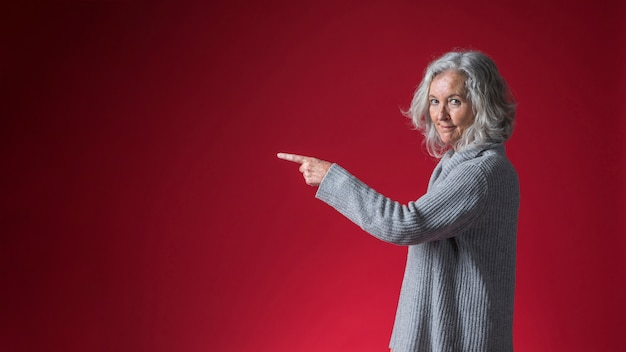 Portret van een glimlachende hogere vrouw die haar vinger richt tegen rode achtergrond