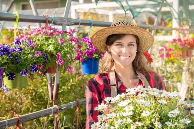 Portret van een glimlachende jaren '30 vrouw in een kas kwekerij werknemer met bloemen in de lente