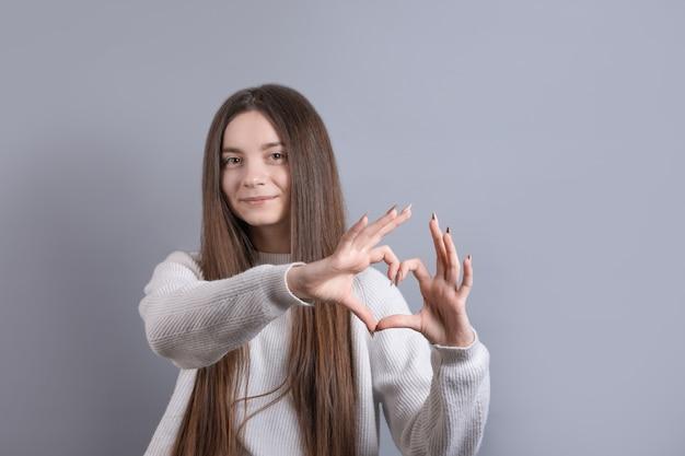 Portret van een glimlachende jonge aantrekkelijke vrouw die hartgebaar met twee handen toont en camera bekijkt die over grijze achtergrond wordt geïsoleerd