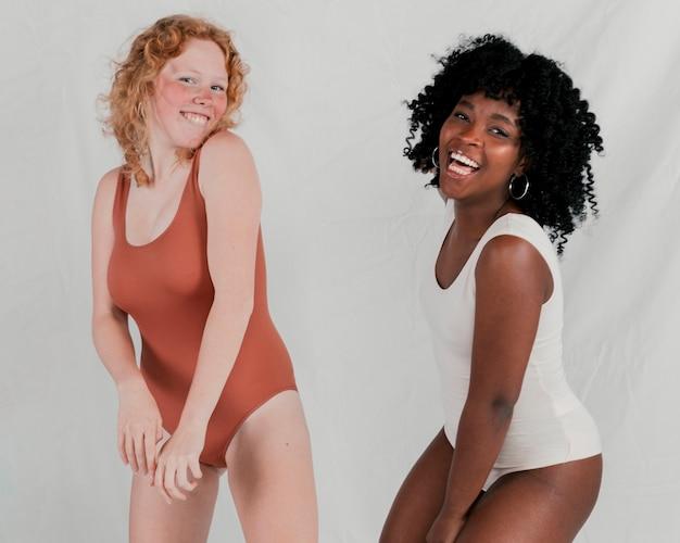 Portret van een glimlachende jonge afrikaanse en blonde vrouwen tegen grijze achtergrond