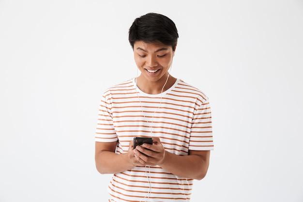 Portret van een glimlachende jonge aziatische man die aan muziek luistert