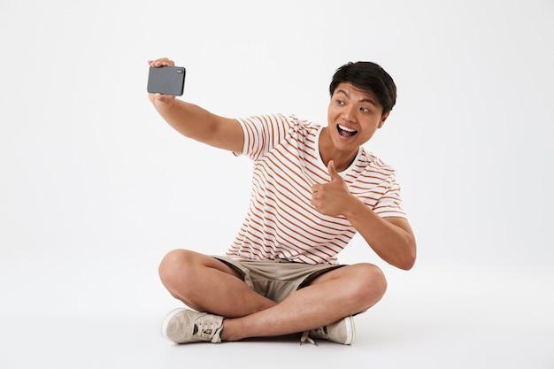 Portret van een glimlachende jonge aziatische man die een selfie neemt