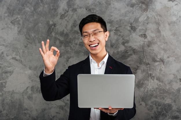 Portret van een glimlachende jonge aziatische man gekleed in pak