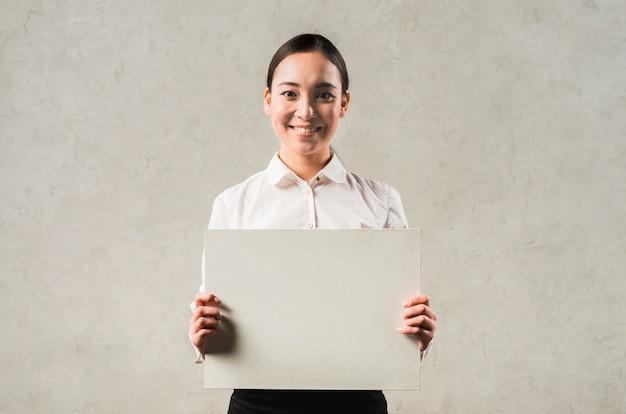 Portret van een glimlachende jonge aziatische onderneemster die leeg aanplakbiljet toont