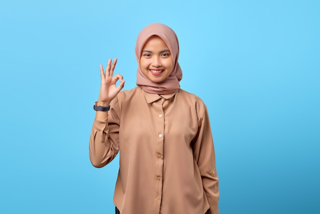 Portret van een glimlachende jonge aziatische vrouw die een goed teken maakt met de vinger over een blauwe achtergrond