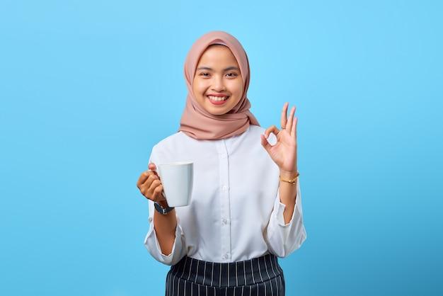 Portret van een glimlachende jonge aziatische vrouw die een goed teken toont en een mok vasthoudt over een blauwe achtergrond