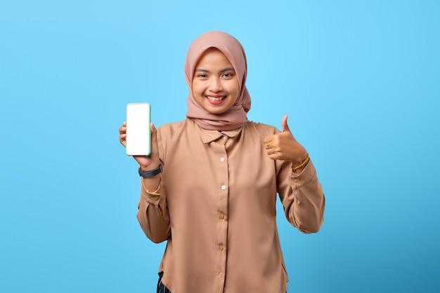 Portret van een glimlachende jonge aziatische vrouw die een leeg scherm van een smartphone laat zien en duimen omhoog doet