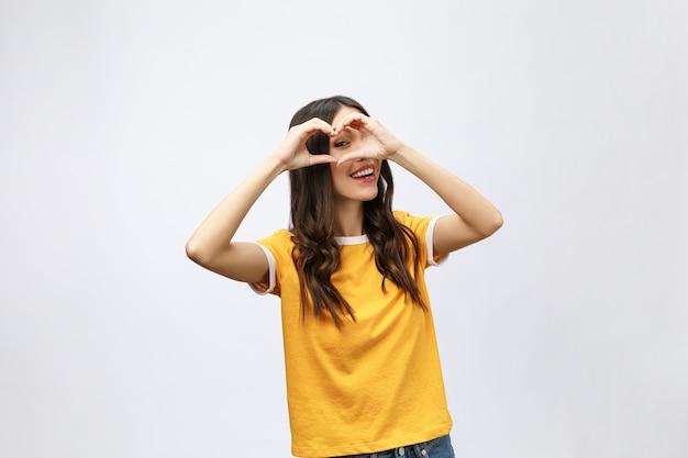 Portret van een glimlachende jonge aziatische vrouw die hartgebaar met twee handen toont