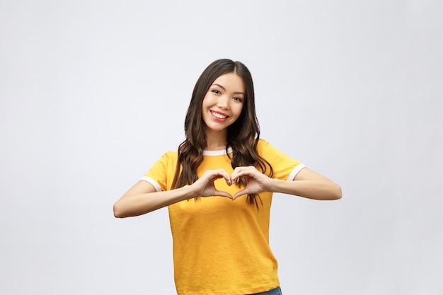Portret van een glimlachende jonge aziatische vrouw die hartgebaar toont