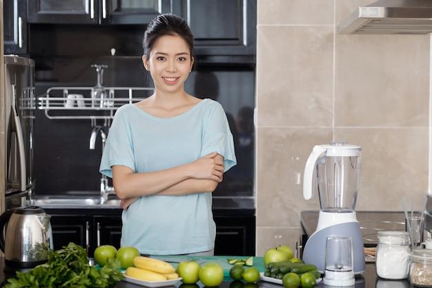 Portret van een glimlachende jonge aziatische vrouw die met gekruiste armen aan het aanrecht staat met smoothie-ingrediënten