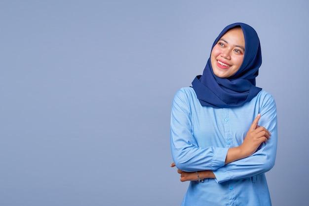 Portret van een glimlachende jonge aziatische vrouw die opkijkt met gekruiste armen