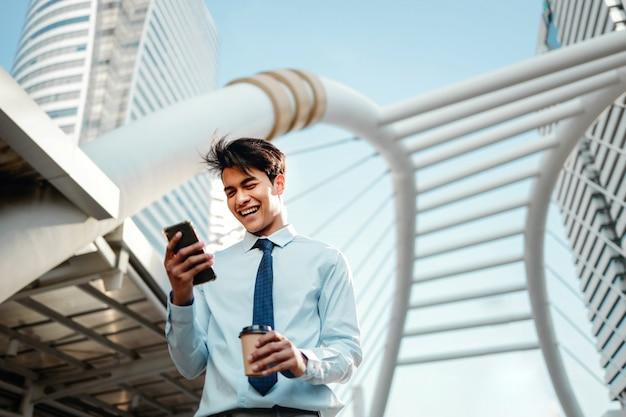 Portret van een glimlachende jonge aziatische zakenman die mobiele telefoon in de stad gebruikt