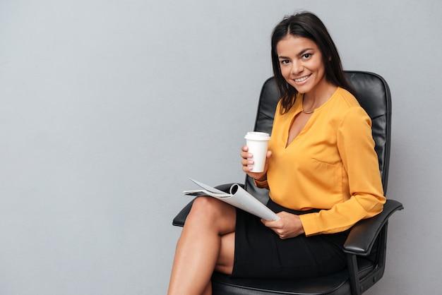 Portret van een glimlachende jonge bedrijfskrant van de vrouwenlezing