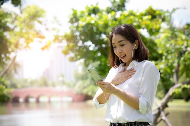 Portret van een glimlachende jonge bedrijfsvrouw die mobiele telefoon in het park met behulp van na het ontspannen werken
