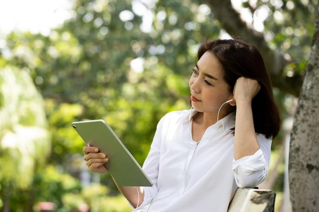 Portret van een glimlachende jonge bedrijfsvrouw die tablet gebruikt voor het luisteren naar muziek in het park