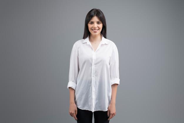 Portret van een glimlachende jonge bedrijfsvrouw in wit die overhemd over grijs wordt geïsoleerd