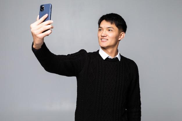 Portret van een glimlachende jonge chinese mens die een selfie met mobiele telefoon nemen terwijl geïsoleerd over witte muur