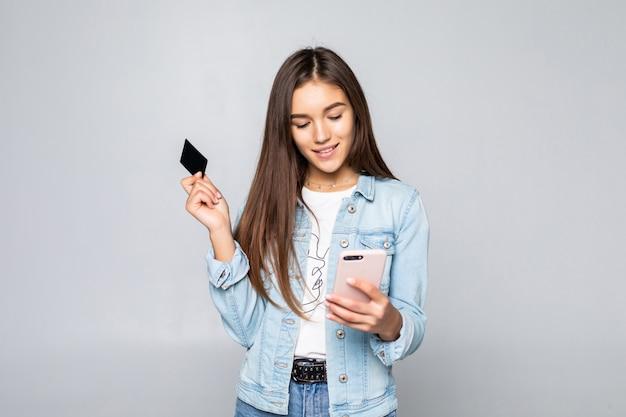 Portret van een glimlachende jonge creditcard van de vrouwenholding die over witte muur wordt geïsoleerd