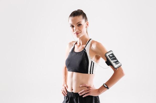 Portret van een glimlachende jonge fitness vrouw in sportkleding