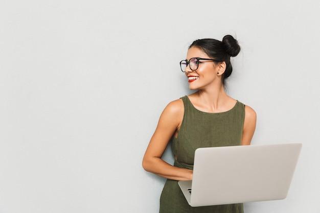 Portret van een glimlachende jonge geïsoleerde vrouw, die laptop met behulp van