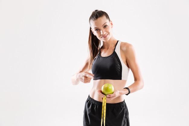 Portret van een glimlachende jonge geschiktheidsvrouw die groene appel houdt