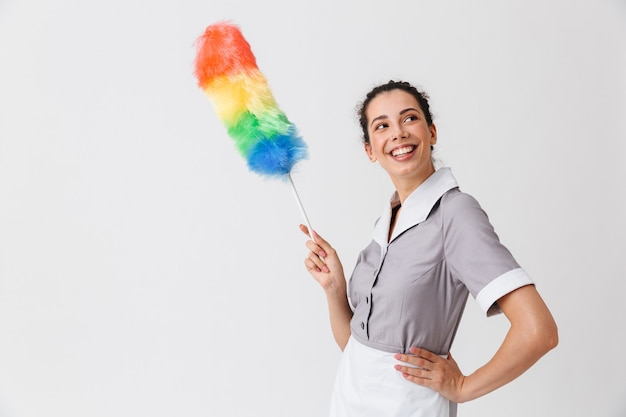 Portret van een glimlachende jonge huishoudster gekleed in uniform