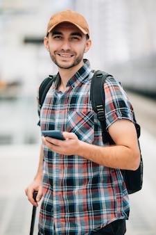 Portret van een glimlachende jonge man die met mobiele telefoon en tas zit te wachten op de trein op het station