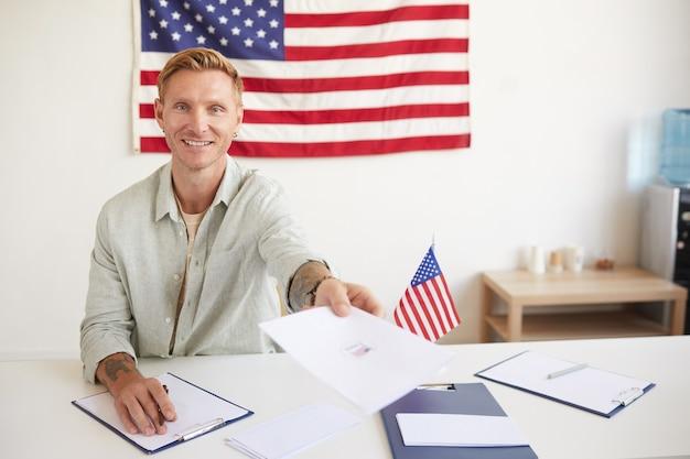 Portret van een glimlachende jonge man die papieren overhandigt aan mensen tijdens het registreren van kiezers bij het stembureau op de dag van de verkiezingen, kopieer ruimte