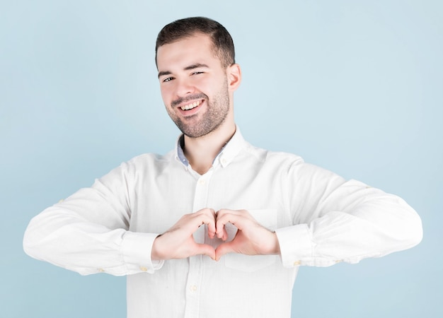 Portret van een glimlachende jonge man die zijn handen op zijn borst houdt in een hartvormig bord, betuigt zijn medeleven. vriendelijke vriendelijke aardige vent in een leeg wit overhemd