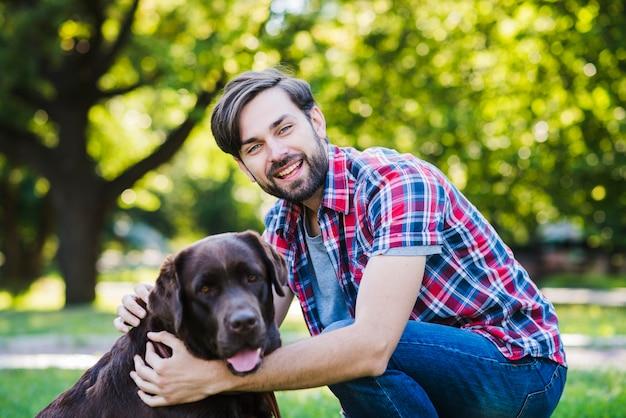 Portret van een glimlachende jonge man en zijn hond in park
