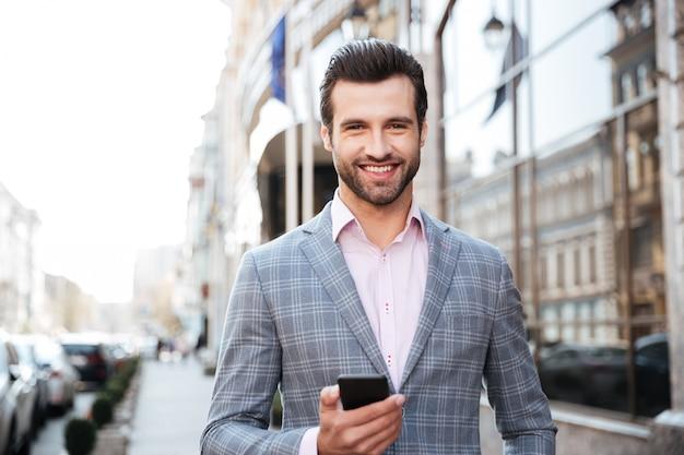Portret van een glimlachende jonge man in de jas