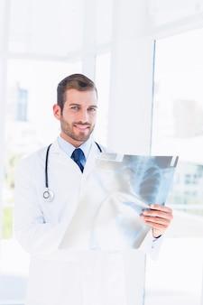 Portret van een glimlachende jonge mannelijke arts die röntgenstraal onderzoekt