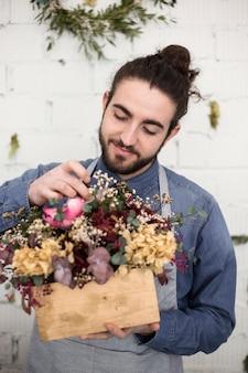 Portret van een glimlachende jonge mannelijke bloemist die de bloemen in de houten doos schikken