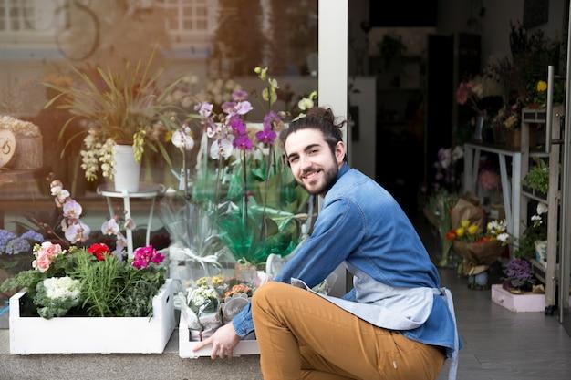 Portret van een glimlachende jonge mannelijke bloemist die de bloemen in de krat schikken