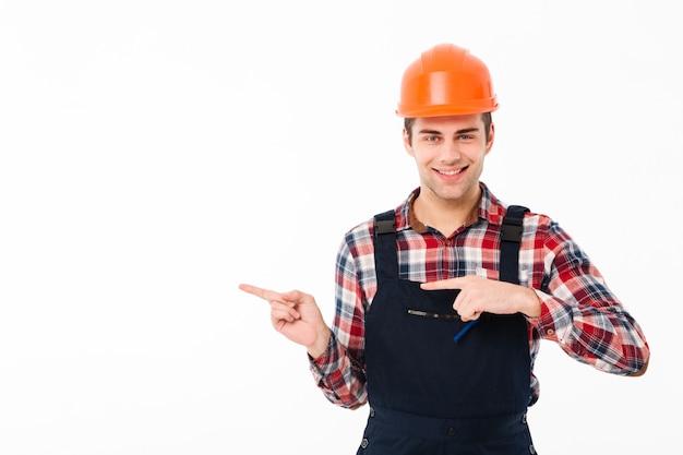 Portret van een glimlachende jonge mannelijke bouwer wijzen